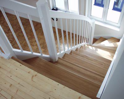 Eingestemmte Holzwangentreppe, Stufen Eiche lackiert, Wangen und Geländer deckend weiß lackiert